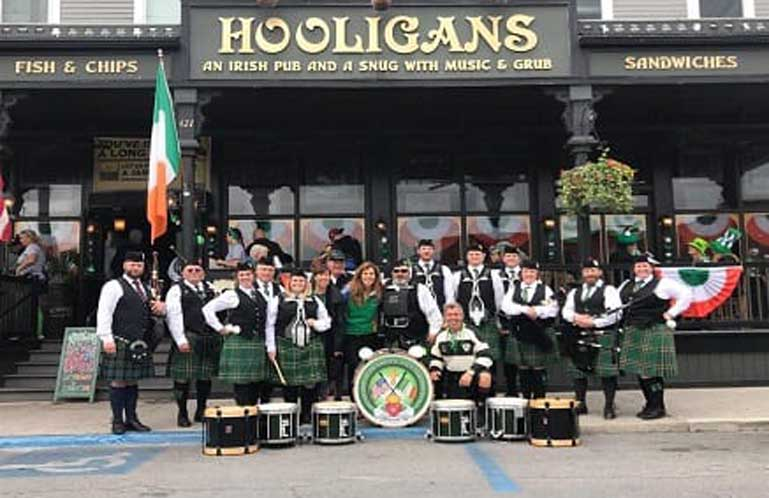 Hooligans Irish Pub - Store front view of Hooligans with several people outside dressed in irish clothing.